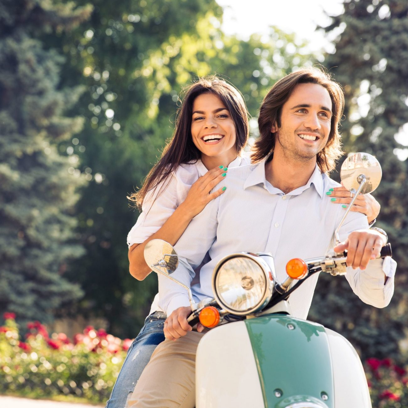 cheerful-young-couple-riding-scooter-town-with-fun