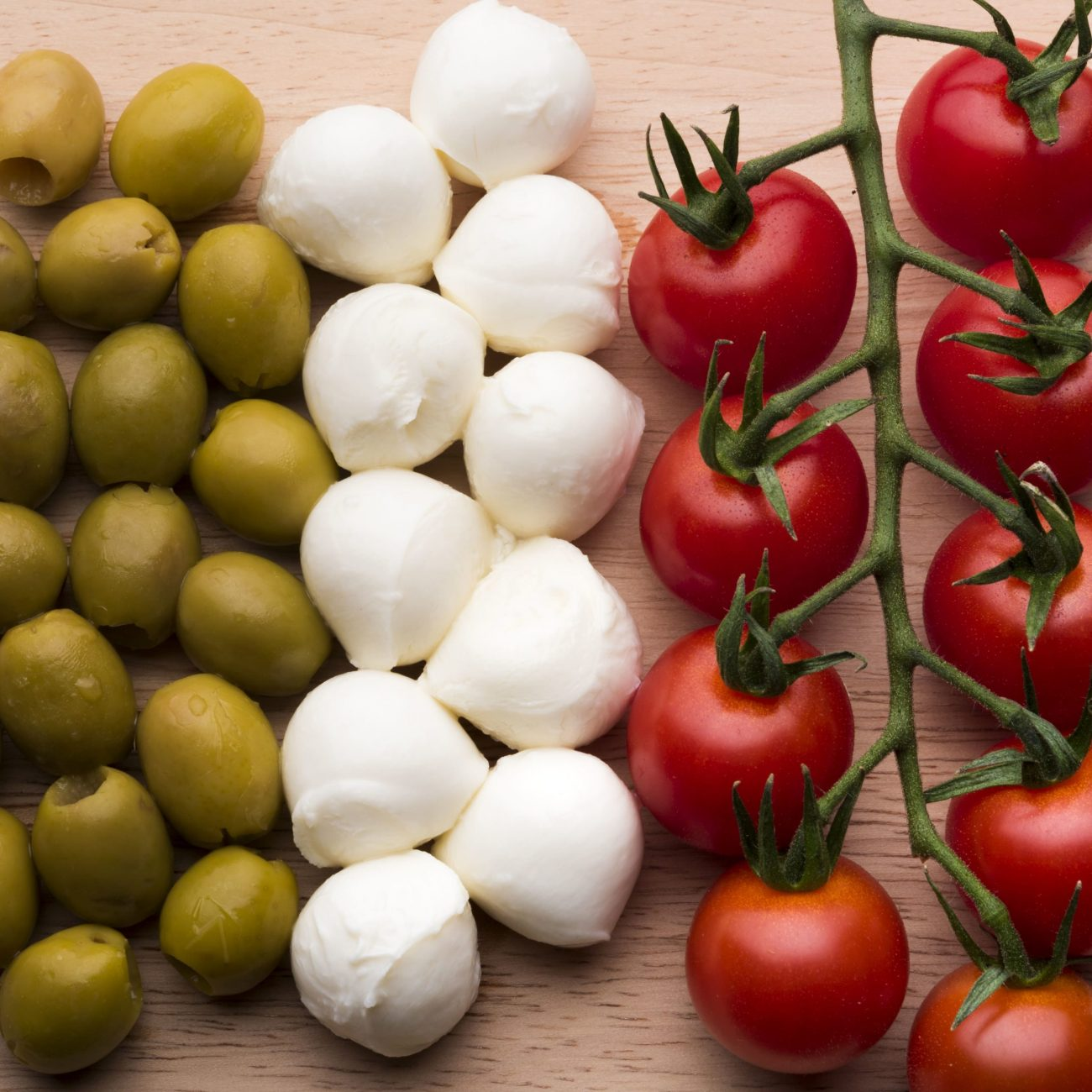 delicious-mozzarella-cheese-fresh-red-tomatoes-wet-olives-wooden-table